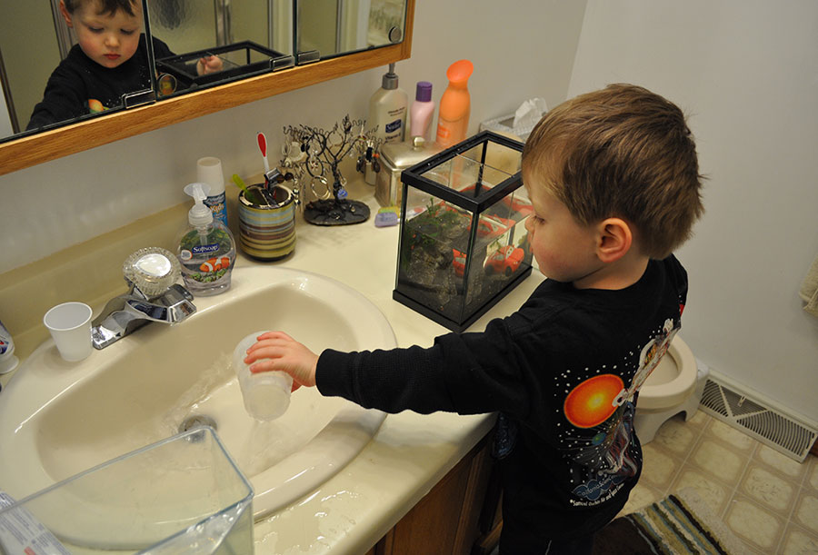 Ethan manually removing 50% of his aquarium water.
