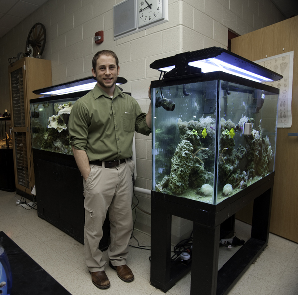 7th Grade Biology Teacher Dwayne Kalinay stands between two of the reef tanks in his classroom.