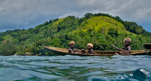 Kids in dugout canoe in the Coral Triangle: their futures depend on healthy reefs and biodiversity.