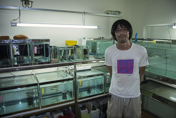 Tomoyuki Sato standing proudly before his home laboratory and fishroom