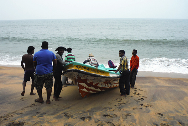 A team of collectors returning from a dive, hauling their boat up on shore