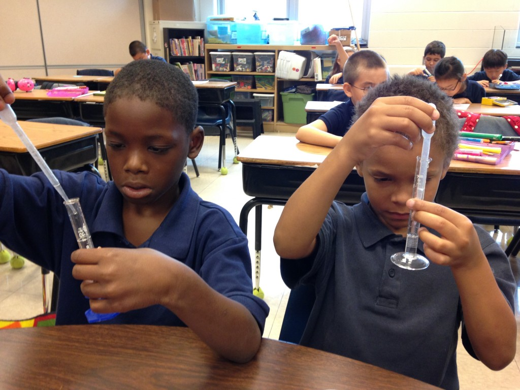 Two male students are using pipettes and graduated cylinders to measure liquids