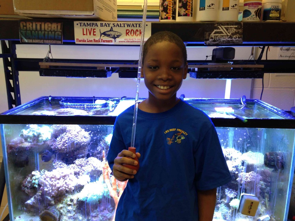 Leon stands in front of the tank that he cares for in his classroom.