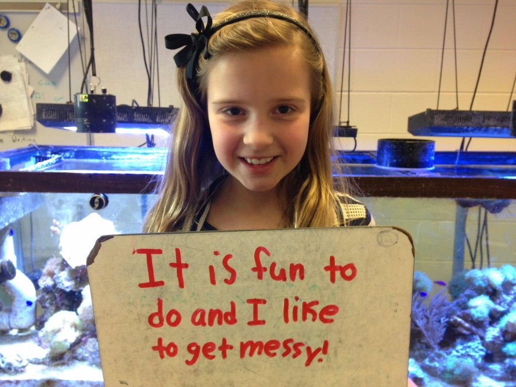 A student from Robeson Elementary visits the coral reef project on Saturday and is asked to define science.