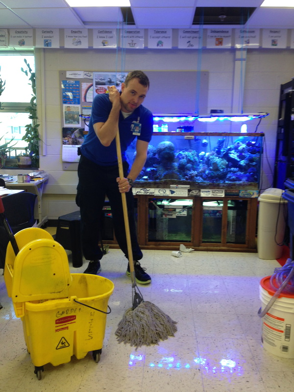 A male teacher is standing in front of an aquarium with a mop, looking tired. The teacher was working overtime to clean up spilled water caused by a student mistake. A float switch on the water reservoir solved this problem.