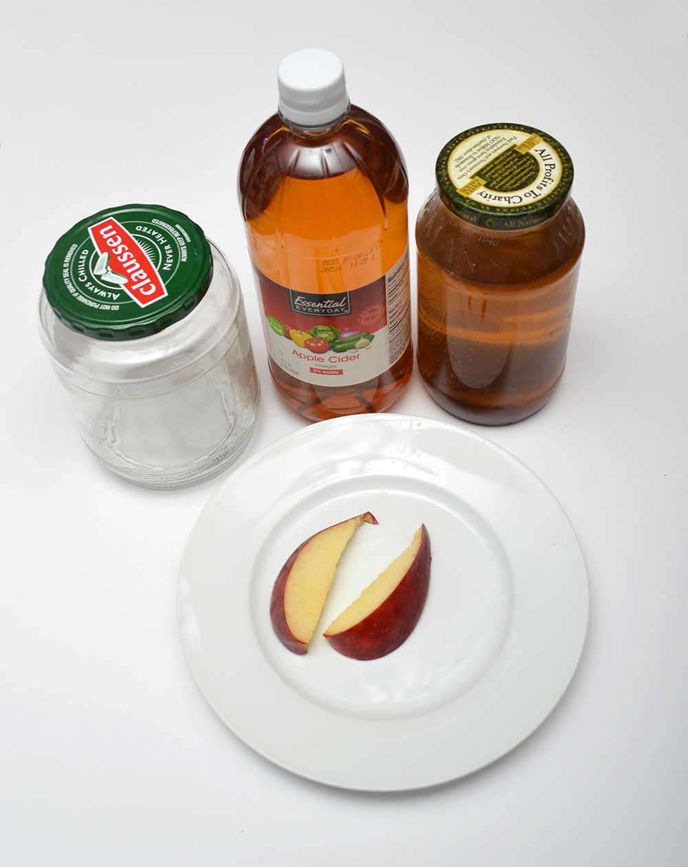The raw materials to make a new culture - clean glass jar, apple cider vinegar, a slice of apple, and a starter culture.