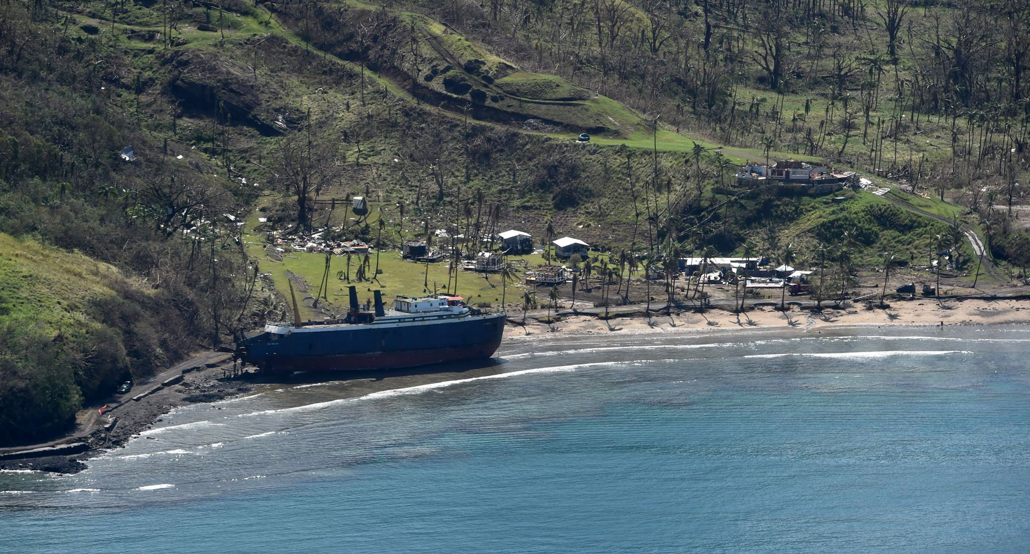 "In the wake of Tropical Cyclone Winston, a large boat, possible identified as the ""Sinu Wasa II"" rests on the beach in front of washed out roads and gutted buildings in the city of Toki, Fiji. Image by NZ Defense Airforce"