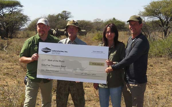 Company representatives present a check to Mark of the Rhino preserve in South Africa