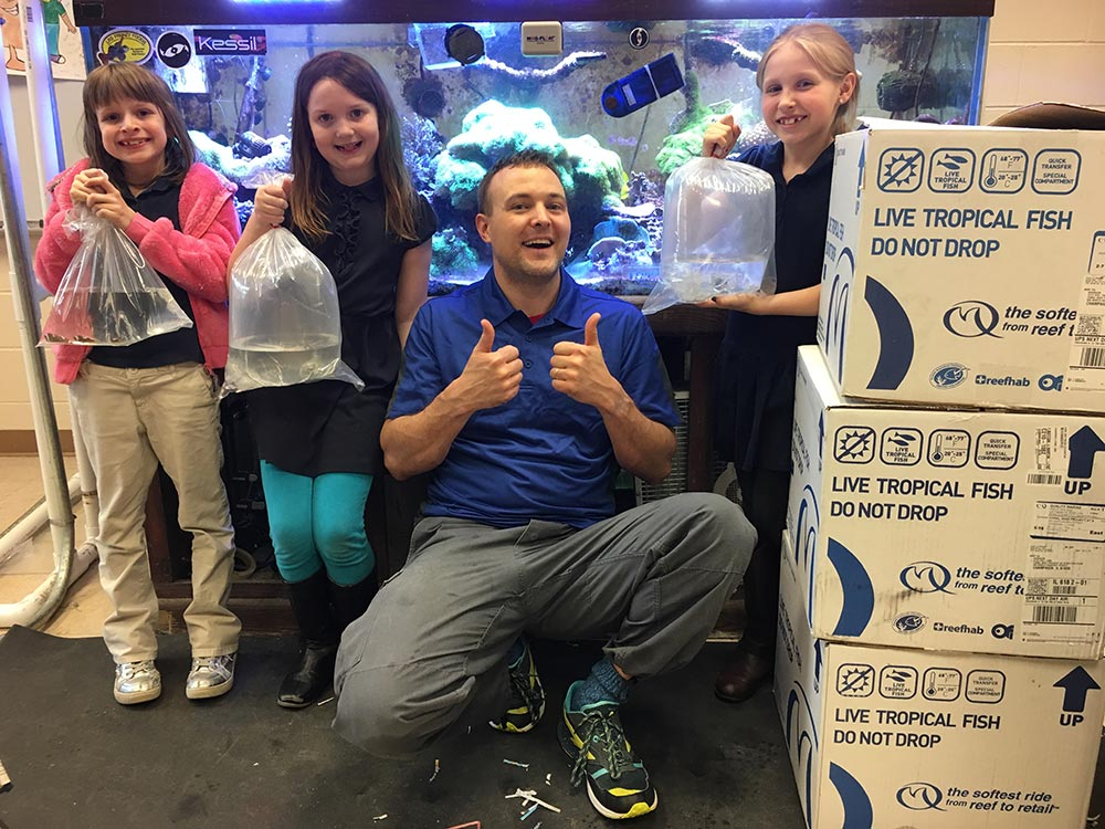 Brandon Rutherford (center right) and students pose with clownfish ready to ship to Quality Marine.