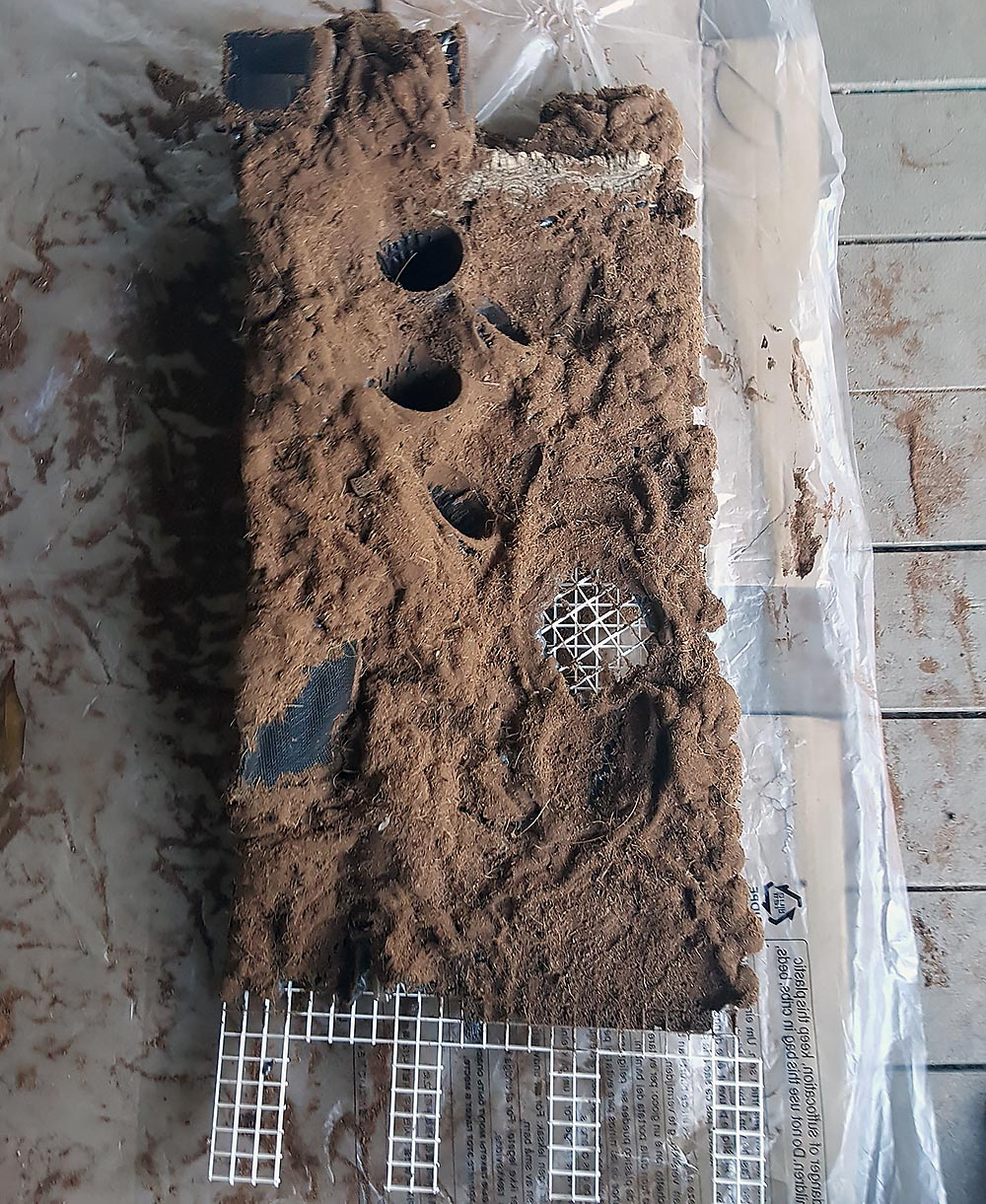 The foundation for the back wall of the vivarium, now foamed and covered to create a natural backdrop while concealing the air circulation system and drainage for the pots. Note the three cutouts at the base, in place to accommodate the bulkheads that move water and handle excess from the water under the false bottom.