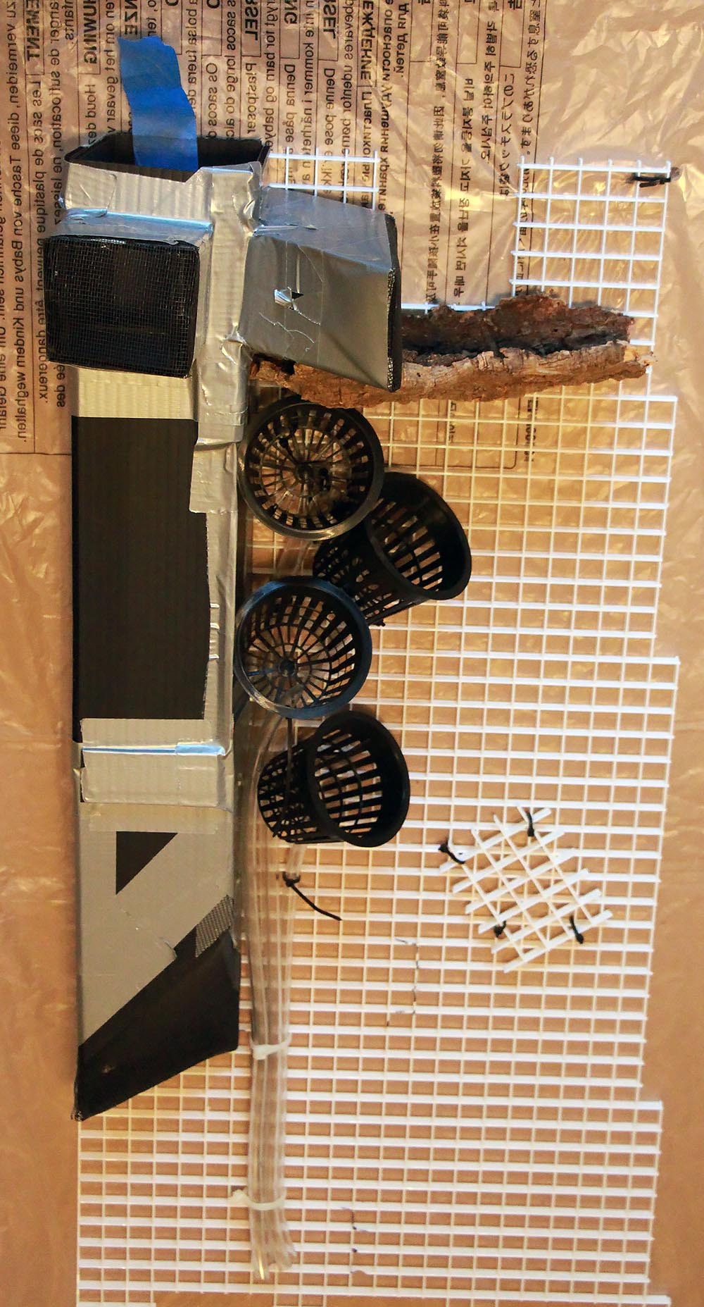 Orchids generally require air movement to prevent disease. This is a great look at the internal ductwork for internal air circulation, constructed out of corrugated plastic. Air is brought in underneath, then circulated by a computer fan and exhausted in two directions at the top. Also, note the pots which include draining tubes to bring excess water down to the substrate and eventually the water table underneath the false bottom.