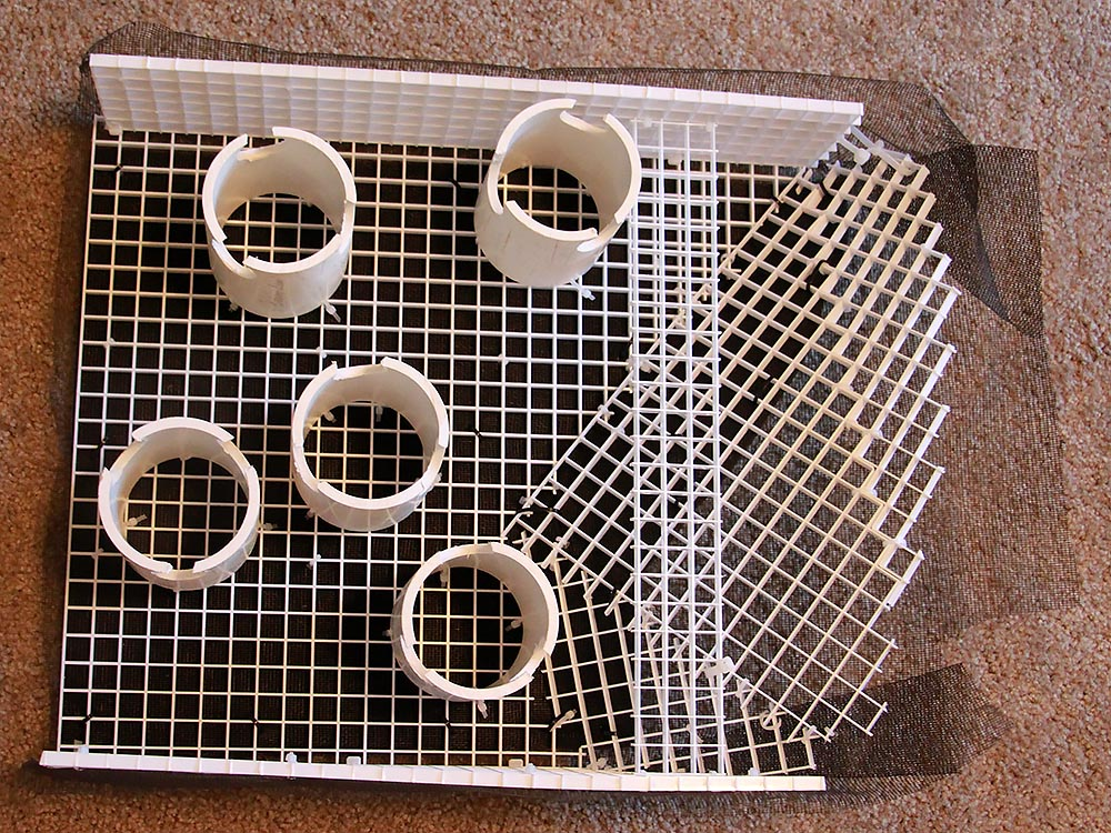 The underside of the false bottom reveals sections of PVC pipe used as support legs. Note the notches cut in the bottoms; this allows water to flow down, through, and out of the pipes.
