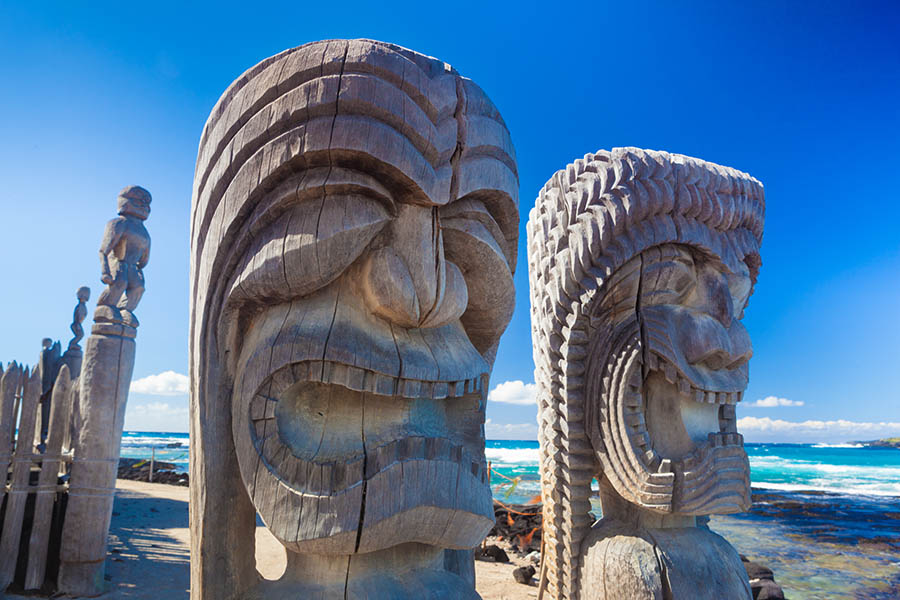 Traditional Hawaiian wood carving of guards at ancient Hawaiian site Pu'uhonua O Honaunau National Historical Park on Big Island, Hawaii. Image credit: George Burba/Shutterstock