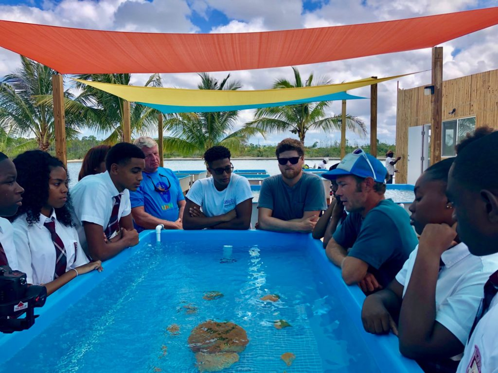 Students and others gather around a coral raceway with Coral Vita co-founder Gator Halpern (center right) in late May, 2019.