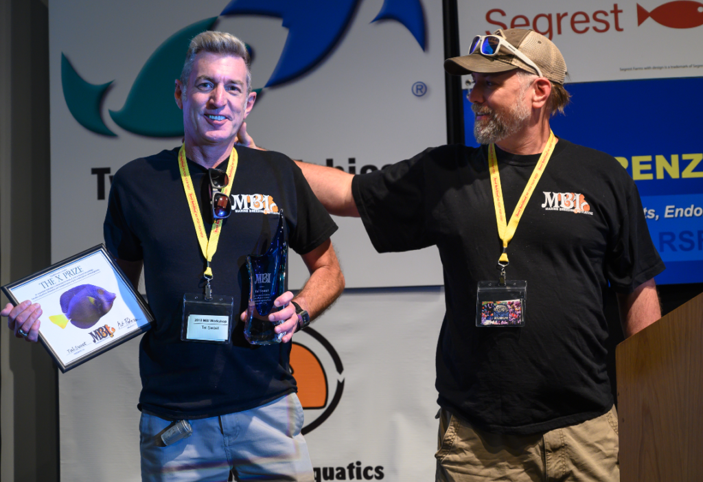 A pat on the back for a decade of marine ornamental aquaculture stewardship, Matt Pedersen (right) had the honor of presenting Tal Sweet with the Marine Breeding Initiative's X-prize and MBI Awards at the 2019 conference.