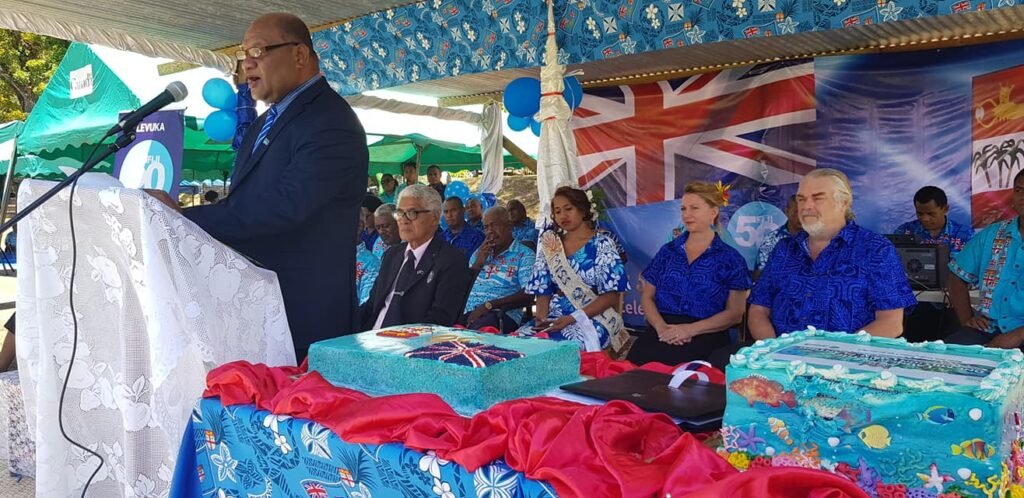 Forestry Minister Naiqamu formally introducing the project at the October 10th, 2020 event. A.D.E. Project co-directors Deb and Walter Smith are seated behind the minister (both in vibrant blue attire).